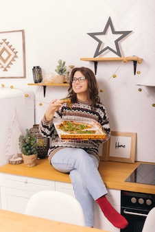 Mooie jonge vrouw die een doos pizza vasthoudt, eet een plakje in de keuken.