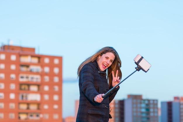 Mooie jonge vrouw die een foto met een selfiestok neemt bij zonsondergang