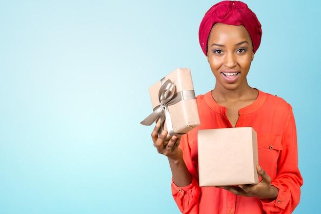 Mooie jonge vrouw die een geschenk houdt