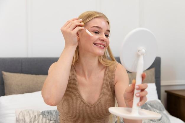 Mooie jonge vrouw die een gezichtsverzorgingsolie gebruikt