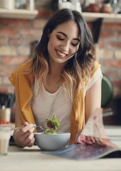 Mooie jonge vrouw die een gezonde salade eet en een tijdschrift leest