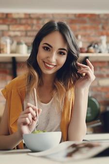 Mooie jonge vrouw die een gezonde salade eet