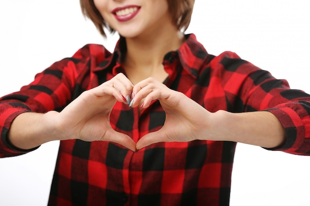 Mooie jonge vrouw die een hartteken toont.