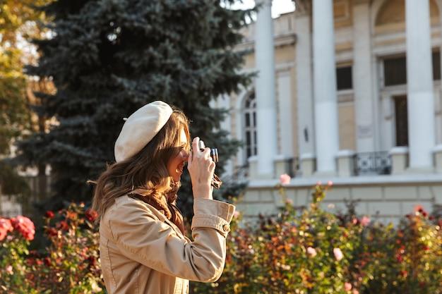 Mooie jonge vrouw die een jas draagt die buiten loopt, met fotocamera