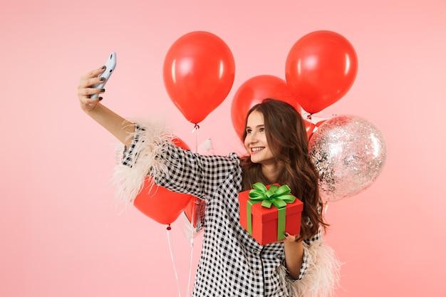 Mooie jonge vrouw die een jas draagt die zich geïsoleerd over roze achtergrond bevindt, viert, houdt bos van ballons vast, neemt een selfie