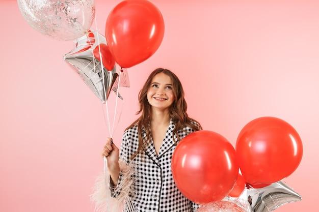 Mooie jonge vrouw die een jas draagt die zich geïsoleerd over roze achtergrond bevindt, viert, houdt bos van ballons vast