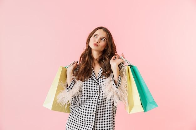 Mooie jonge vrouw die een jasje draagt die zich geïsoleerd over roze achtergrond bevindt, met boodschappentassen