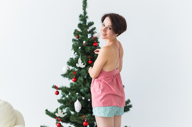 Mooie jonge vrouw die een kerstboom verfraait