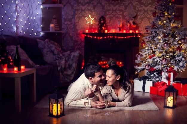 Mooie jonge vrouw die een lief moment heeft met haar vriendje in de woonkamer bij de kerstboom. kerst viering.