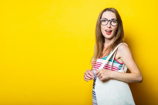 Mooie jonge vrouw die een linnenzak met aankopen op een gele achtergrond onderzoekt.
