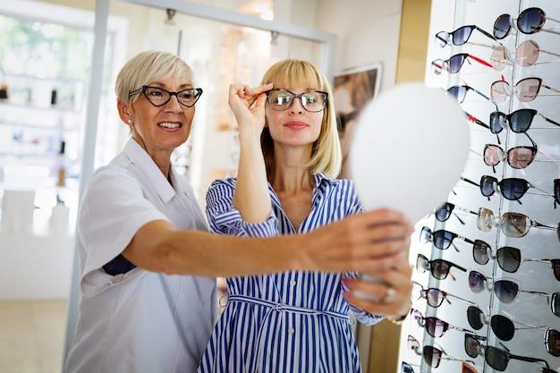 Mooie jonge vrouw die een nieuwe bril kiest in de winkel van opticiens. gezichtscorrectie. optiek. oogheelkunde.