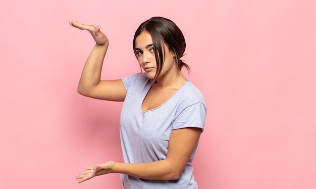 Mooie jonge vrouw die een object vasthoudt met beide handen op de zijkopieerruimte, een object toont, aanbiedt of adverteert