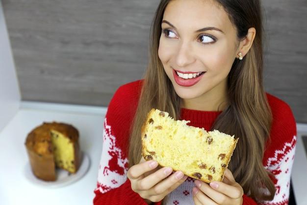 Mooie jonge vrouw die een plakje panettone eet tijdens de kerstvakantie