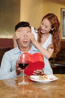 Mooie jonge vrouw die een romantische verrassing maakt voor haar vriendje op valentijnsdag