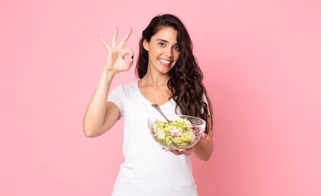Mooie jonge vrouw die een salade bereidt