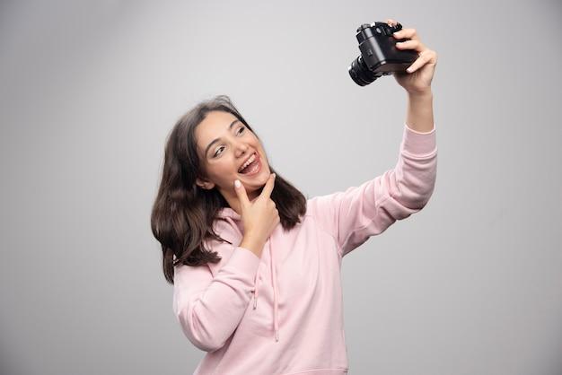 Mooie jonge vrouw die een selfie met camera neemt over een grijze muur.