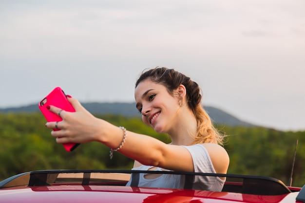 Mooie jonge vrouw die een selfie neemt terwijl u geniet van een reis.