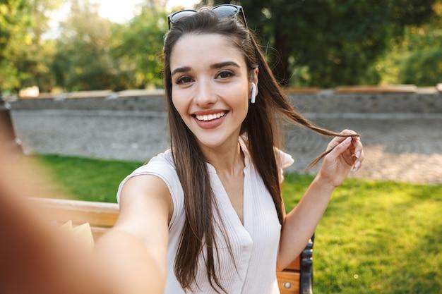 Mooie jonge vrouw die een selfie zittend op een bankje met boodschappentassen buitenshuis