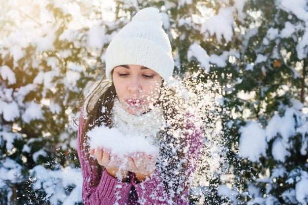 Mooie jonge vrouw die een sneeuw houdt en erop blaast