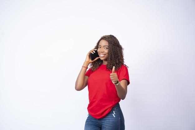 Mooie jonge vrouw die een telefoongesprek voert en een duim omhoog geeft