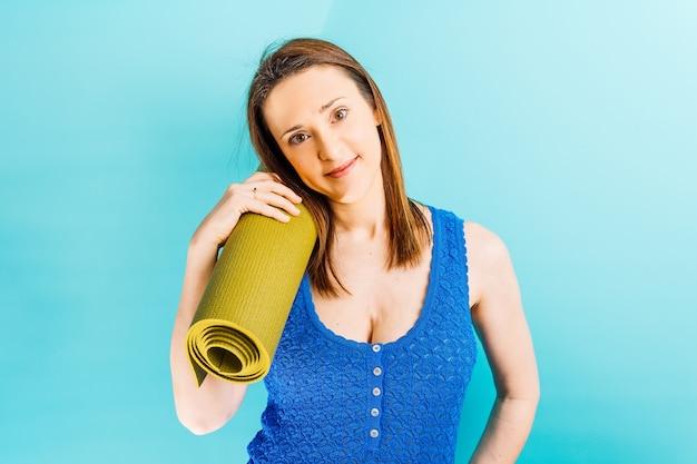 Mooie jonge vrouw die een yogamat op blauwe achtergrond houdt. concept persoonlijke verzorging sport stretching