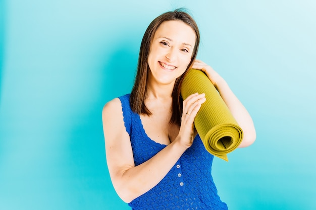 Mooie jonge vrouw die een yogamat op blauwe achtergrond houdt. stretching sport persoonlijke verzorging concept
