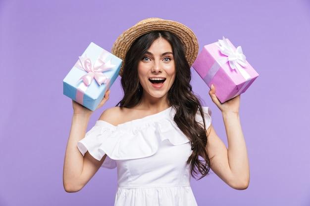 Mooie jonge vrouw die een zomeroutfit draagt, geïsoleerd over een violette muur, met twee geschenkdozen