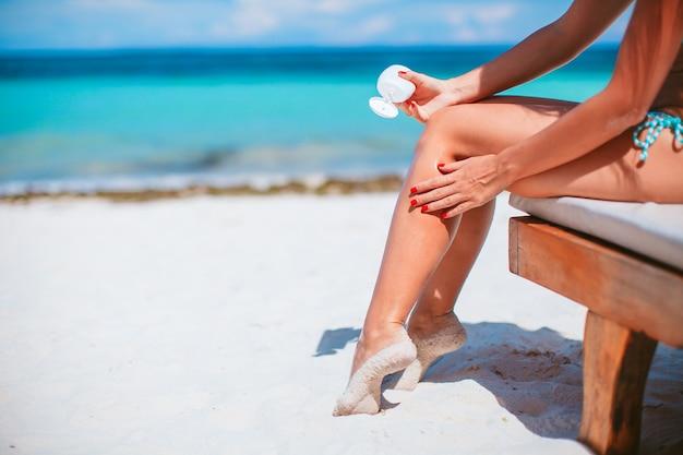 Mooie jonge vrouw die een zonnebrandcrème houdt die op tropisch strand ligt