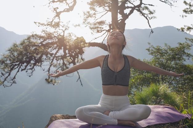 Mooie jonge vrouw die en bovenop hem mediteert uitoefent.