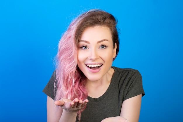 Mooie jonge vrouw die en de palm van haar hand glimlacht toont