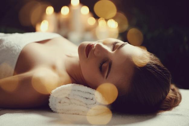 Mooie jonge vrouw die en op haar massage ligt te wachten. spa concept