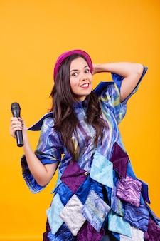 Mooie jonge vrouw die funky kleren draagt en microfoon zingt. plezier hebben