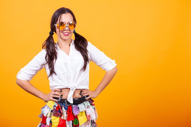 Mooie jonge vrouw die funky kostuum over gele achtergrond draagt. dwaze stemming