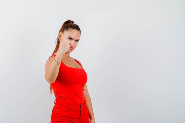 Mooie jonge vrouw die gebalde vuist in rood mouwloos onderhemd, broek toont en hatelijk, vooraanzicht kijkt.