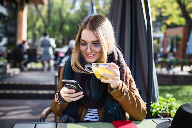 Mooie jonge vrouw die geniet in de cafetaria, iets naar de telefoon kijkt en thee drinkt