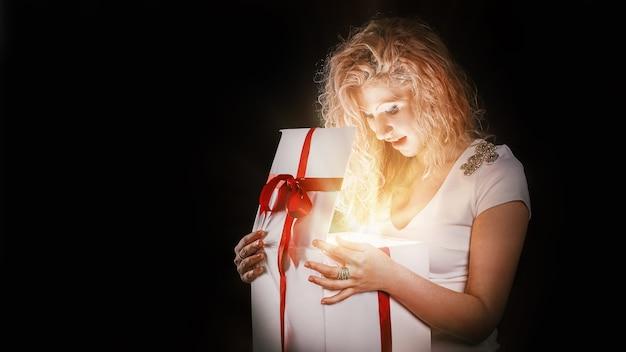 Mooie jonge vrouw die geschenkdoos opent. geïsoleerd op zwarte achtergrond