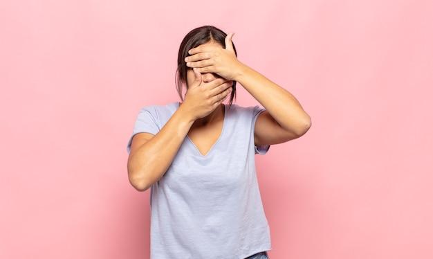 Mooie jonge vrouw die gezicht bedekt met beide handen die nee zeggen tegen de camera! afbeeldingen weigeren of foto's verbieden