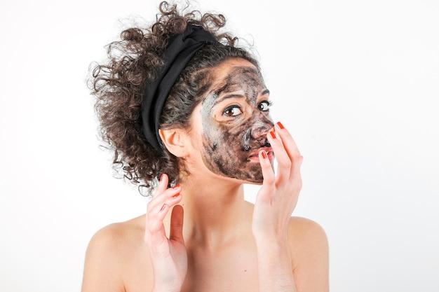 Mooie jonge vrouw die gezichtsmasker op haar gezicht over witte achtergrond toepast