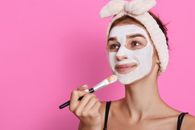 Mooie jonge vrouw die gezichtsmasker thuis toepast