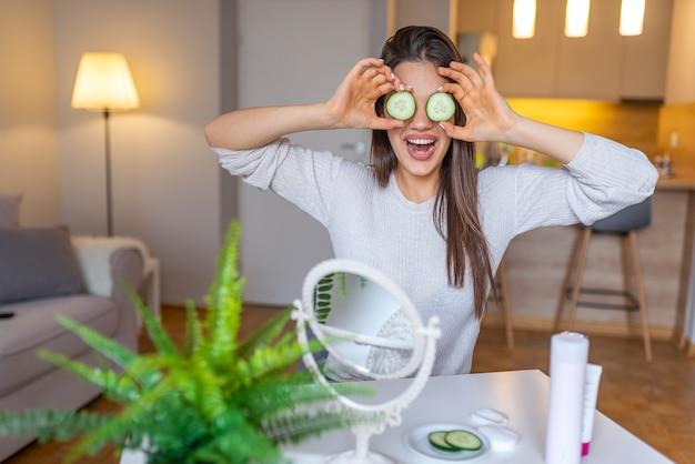 Mooie jonge vrouw die gezichtsmasker van komkommer thuis ontvangt.