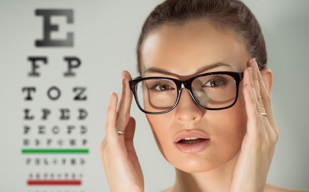 Mooie jonge vrouw die glazen draagt die zich voor oogtest bevinden