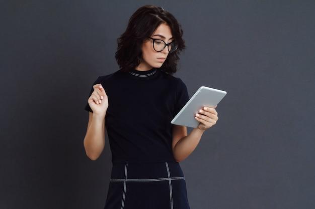 Mooie jonge vrouw die glazen dragen die over grijze muur stellen en tablet in handen houden