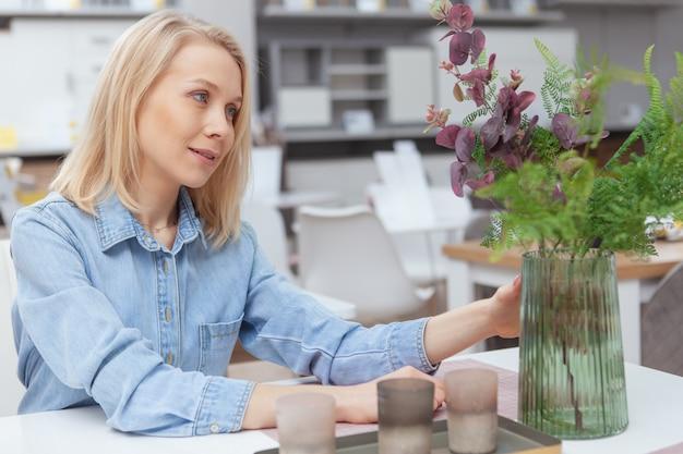 Mooie jonge vrouw die groene installaties op de vaas onderzoeken, die thuis goederenopslag winkelen