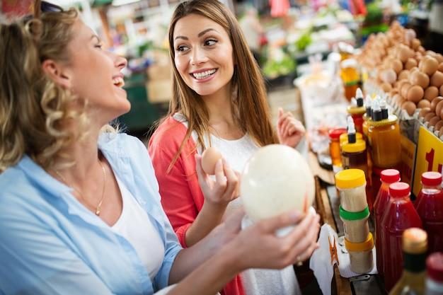 Mooie jonge vrouw die groenten en fruit op de markt winkelt