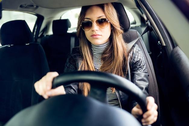 Mooie jonge vrouw die haar auto rijdt.
