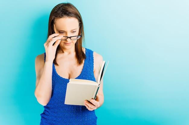 Mooie jonge vrouw die haar bril opzet terwijl ze een boek op een blauwe achtergrond probeert te lezen
