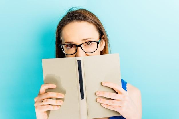 Mooie jonge vrouw die haar gezicht bedekt met een boek met een blauw achtergrondleesconcept
