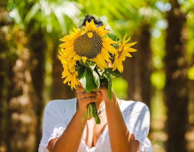 Mooie jonge vrouw die haar gezicht verbergt achter een boeket zonnebloemen