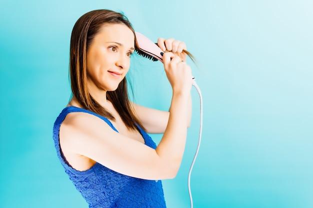 Mooie jonge vrouw die haar haar borstelt met ionen elektrische föhnborstel met blauwe achtergrond