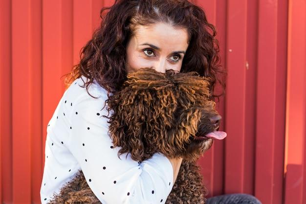 Mooie jonge vrouw die haar hond, een bruine spaanse waterhond koestert over rode achtergrond. ze lacht en houdt van de hond. liefde voor dieren